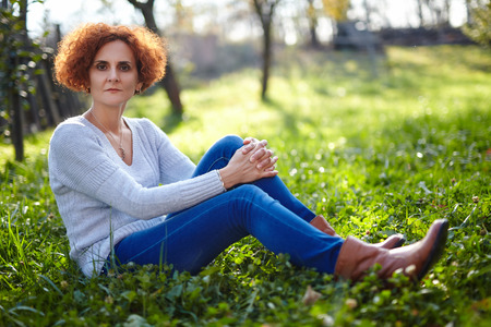 Caucasian lady farmer in jeans sitting in the grass at sunset photo