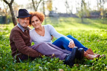Old farmer and his daughter sitting in the grass, resting photo