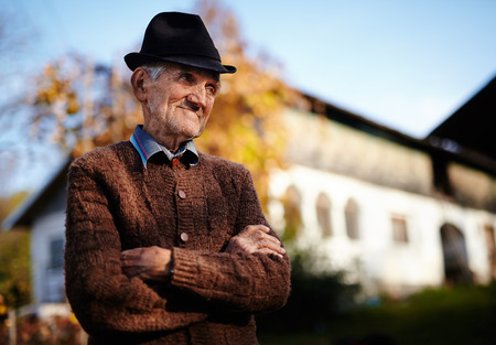 Happy Romanian senior farmer near a traditional house, at sunset photo