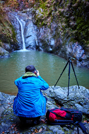 Nature photographer shooting a waterfall in the mountains photo