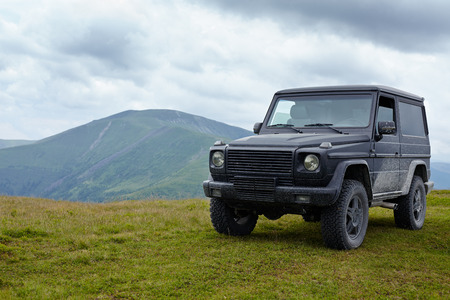 Off road car in a mountain environment on a meadow