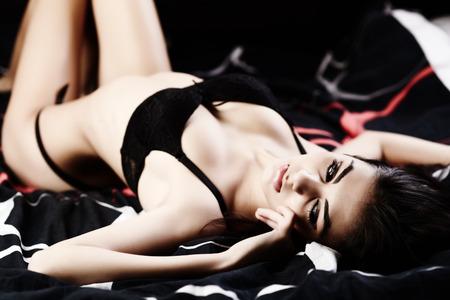 Glamourous lingerie model on bed, studio shot photo