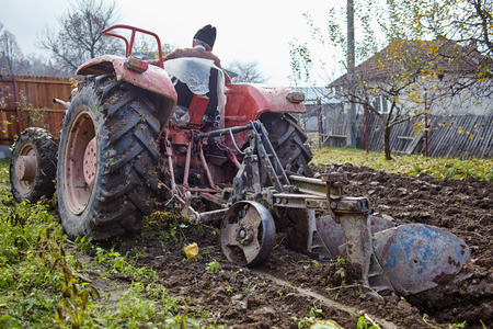 Senior farmer on an old red tractor plowing his garden in the backyard photo