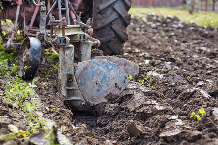 Image from the back of a tractor plowing the land, focus is on plow photo