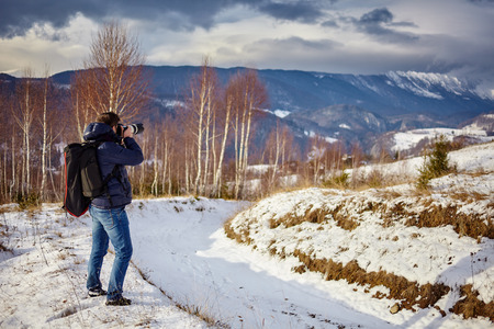 winter photos: Tourist taking photos of mountains at sunset in a winter evening Stock Photo