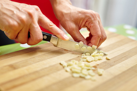 garlic clove: Woman hands chopping garlic on a wooden board