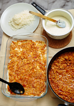 Lasagna preparation with filling in a frying pan and tray, grated parmesan and bechamel sauce photo