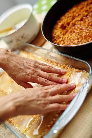 Woman cooking lasagna, arranging the pasta in a tray with filling photo