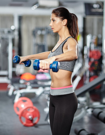 deltoids: Young fitness woman doing deltoids workout with dumbbells in a gym