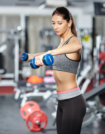 Young fitness woman doing deltoids workout with dumbbells in a gym
