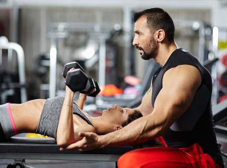 personal trainer woman: Personal fitness trainer assisting a young woman in the gym at a workout Stock Photo
