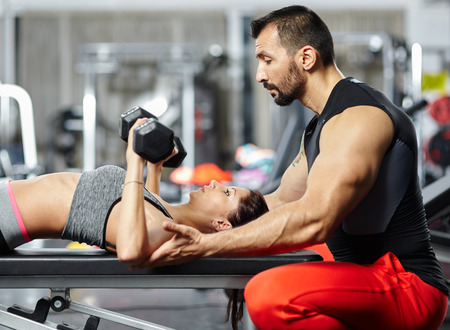 Personal fitness trainer assisting a young woman in the gym at a workout photo
