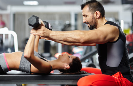 coach sport: Personal fitness trainer assisting a young woman in the gym at a workout Stock Photo