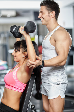 Personal fitness instructor helping a young woman doing workout with dumbbells photo