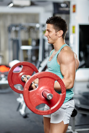 Fitness man doing biceps workout with barbell in a gym photo
