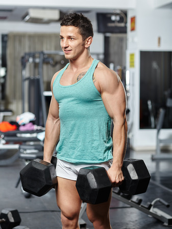 trapeze: Strong fit man doing shoulder and trapeze workout with very heavy dumbbells