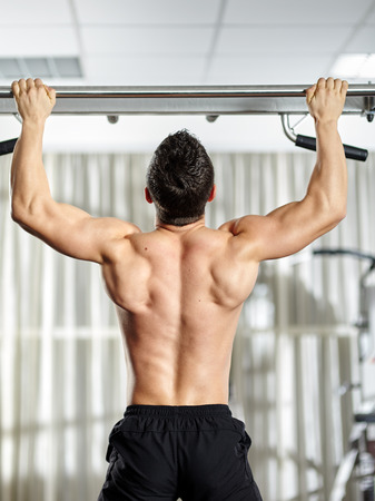 pullups: Fitness man doing pull-ups in a gym for a back workout Stock Photo