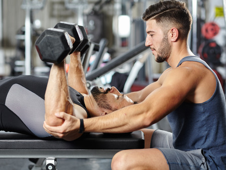 gyms: Personal fitness trainer helping a man at a chest workout with heavy dumbbells