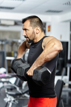 Fitness athletic sportsman doing shoulder workout with dumbbells in a gym