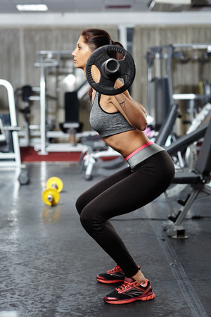 Young fitness woman doing barbell squats in a gym