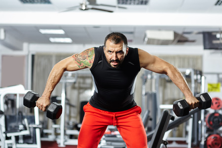 Fitness athletic sportsman doing shoulder workout with dumbbells in a gym photo
