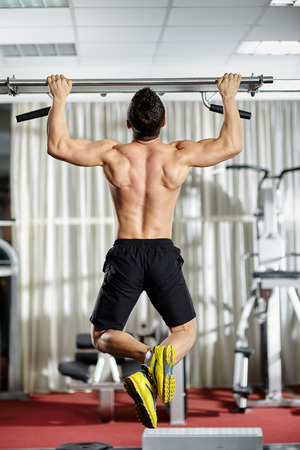 Fitness man doing pull-ups in a gym for a back workout photo