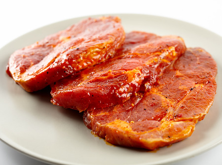 Marinated and seasoned pork neck slices on a plate