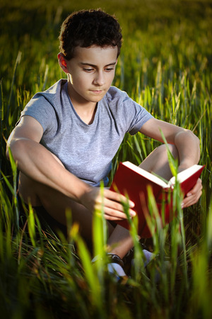 captivated: Closeup of a teenage boy reading a book in a wheat field at sunset, with selective focus