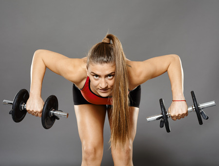 deltoid: Young caucasian fitness woman working with dumbbells, studio shot