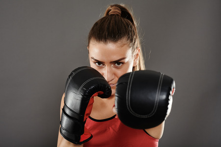 jab: Kickbox girl delivering a left jab, studio shot Stock Photo