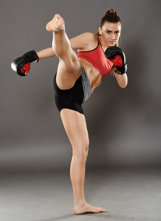 female kick: Kickbox young woman delivering a kick, over gray background