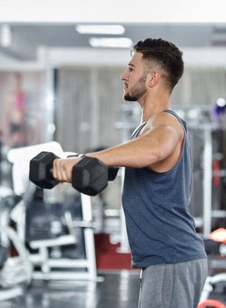 Athletic slim young man working out with dumbbells in a gym Stock Photo