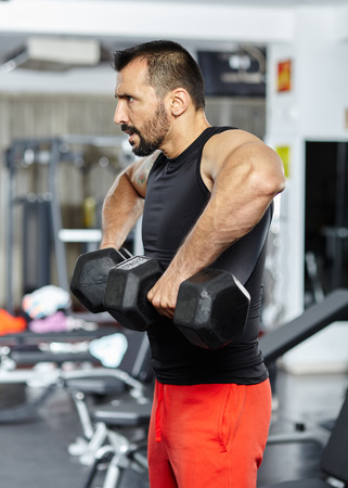 Fitness man doing shoulder workout with dumbbells in a gym
