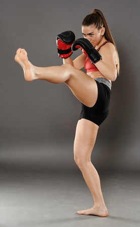 girl kick: Kickbox young woman delivering a kick, over gray background