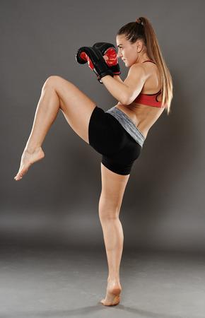 patada: Chica Kickbox dar un golpe de rodilla, sobre fondo gris