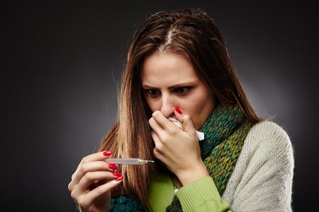 gripe: Primer plano de una mujer joven con gripe mirando el term�metro de la preocupaci�n
