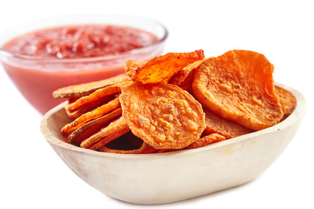 Wooden bowl full with homemade sweet potatoes chips and tomatoes sauce in background, isolated on white photo