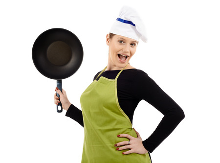 Studio shot of a young woman cook holding a wok pan isolated on white background