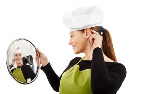 steel pan: Hermosa mujer joven cocinero mirando su reflejo en una tapa de una sart�n de acero inoxidable