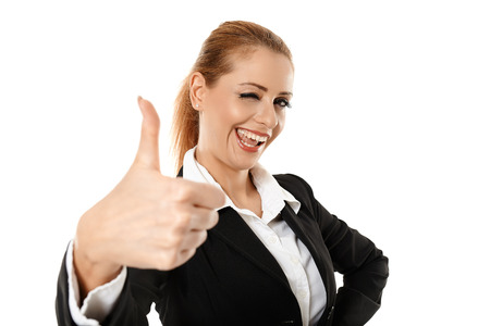 posing  agree: Happy successful businesswoman showing thumbs up and winking at the camera