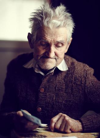 Oude man in zijn jaren '80 die net ontving zijn klein pension, met een peinzende uitdrukking op zijn gezicht Stockfoto