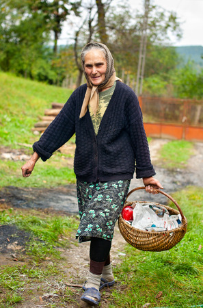 Old peasant woman with basket outdoor Standard-Bild
