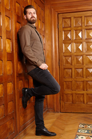 Fashionable bearded man standing in a vintage room with wooden walls photo