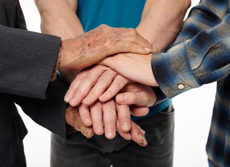 Three generations - grandfather, son and grandson holding hands, giving help and support each other