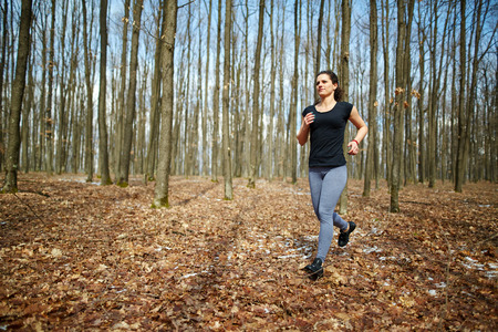 chilly: Young caucasian woman running on a forest trail in a chilly day Stock Photo