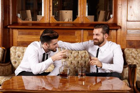 botella de whisky: Dos amigos con una copa de whisky y una agradable conversaci�n Foto de archivo