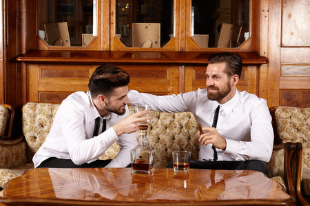 whiskey glass: Two friends having a glass of whiskey and a nice conversation Stock Photo