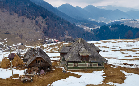 haycock: Traditional Romanian household with mountains on background on wintertime Stock Photo