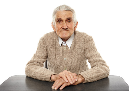 sit studio: Happy 80 years old man sitting at the desk, studio shot Stock Photo