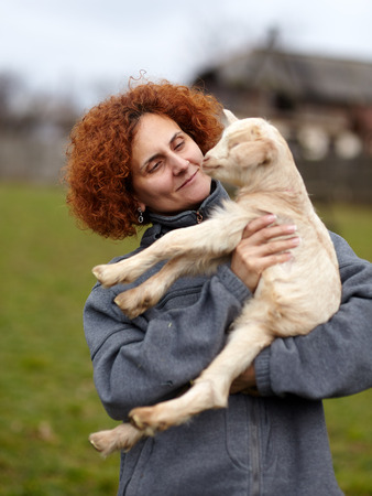 Farmer woman holding a cute baby goat outdoor photo